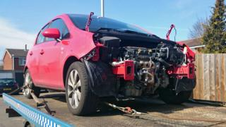 Red vandalised Vauxhall car on a flatbed truck