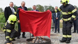 Czech politicians, including President Zeman, hold the giant boxer shorts aloft as two firefighters in full protective gear prepare to burn it in a small fire pit in front of him