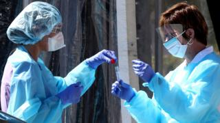 Medical personnel secure a sample from a person at a drive-thru Coronavirus testing station in the US. 12 March 2020