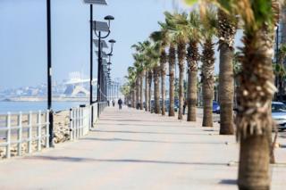 People walk along the empty corniche in Sidon, Lebanon