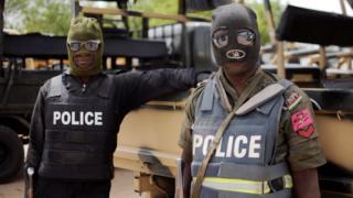 Two Nigerian policemen dey stand dey look