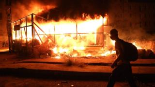 A Lebanese anti-government protester walks past a burning wooden structure during a demonstration against dire economic conditions, in the centre of the capital, Beirut, late on 11 June 2020