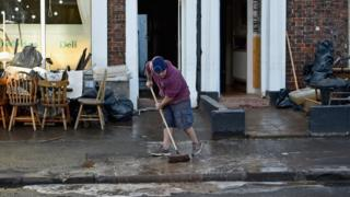 Man sweeps water out of home