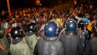 Protesters face security forces during a demonstration