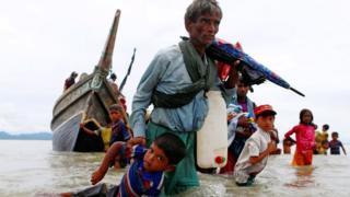 An dauki wannan hoto ne a ranar 5 ga watan Satumba, hoton ya nuna wani dan gudun hijira na kabilar Rohingya ya na rike da hannun wani yaro a lokacin da suke hijira ta hanyar ketara kogi cikin kwale-kwale
