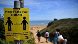 Social distancing reminder sign at a UK beach