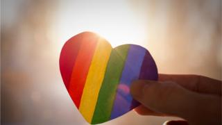 hand holds a heart painted like a LGBT flag, silhouetted against sun