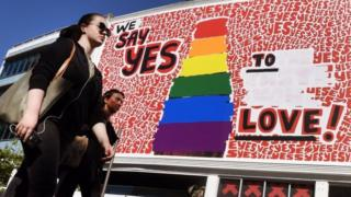 "People walk past a giant billboard promoting the ""yes"" vote for same-sex marriage in Sydney's Kings Cross district (14 November 2017)"