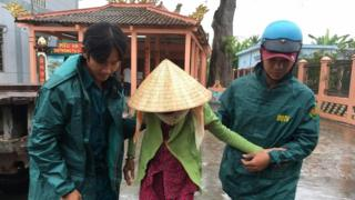 Municipal workers evacuate a local woman as Typhoon Tembin approaches in Ben Tre, Vietnam, 25 December