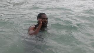 Mvuvi akionyesha wanavyowasiliana kwa simu ndani ya bahari hindi