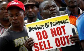 "A protester outside parliament holds a sign reading: ""Members of Parliament: Do not sell out!"""