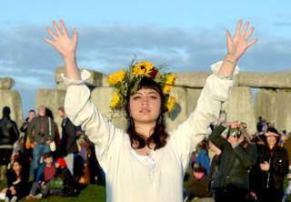 A reveller enjoys the sunrise at Stonehenge in Wiltshire
