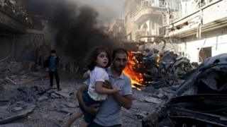 A man carries a girl as they run away from a site hit by what activists said were air strikes by forces loyal to Syria's President Bashar al-Assad in the Douma area of Damascus (24 August 2015)