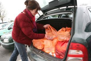 woman puts bags in car boot