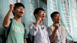 "Leaders of Hong Kong""s ""Umbrella Revolution"" (L to R) Joshua Wong, 19, Nathan Law, 23, and Alex Chow, 25, shout slogans upon their arrival outside the Eastern Court in Hong Kong on August 15, 2016."