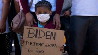 Dareli Matamoros, a girl from Honduras, holds a sign asking President Biden to let her in during a migrant demonstration demanding clearer United States migration policies, at San Ysidro crossing port in Tijuana, Baja California state, Mexico on March 2, 2021