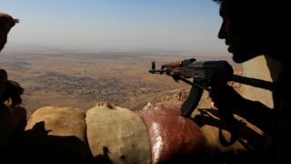 Iraqi Kurdish Peshmerga fighters overlooking a town from the top of Mount Zardak, about 25km east of Mosul