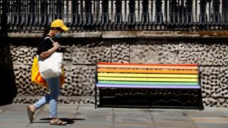 Woman walks past a bench