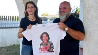 Carla Lucarelli (L) with her partner Angelo Di Ponzo display a T-shirt with the portrait of their son Giorgio, who died in Taranto of a cancer presumed by doctors to be linked to environmental pollution