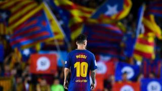 Player Lionel Messi of Barcelona football club looks on as Catalan pro-independence flags are seen in the background