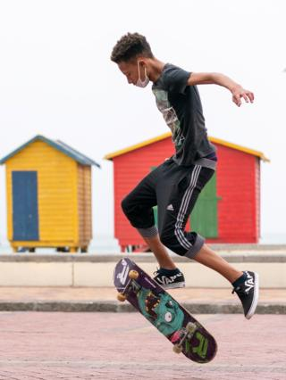 A man skateboarding next to the closed Muizenberg Beach in Cape Town, South Africa - Wednesday 25 March 2020
