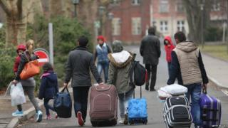 Migrants pulling suitcases outside an asylum registration office in Germany