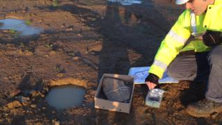 Expert looking at pottery believed to date back to the Iron Age