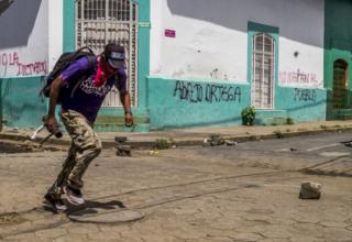 A protester carrying a home-made mortar runs to avoid police snipers in Masaya on 13 June 2018