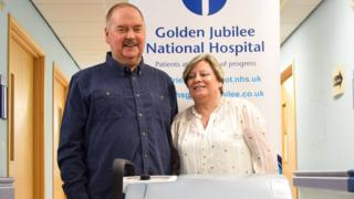 Colin standing next to his wife Susan in the hospital