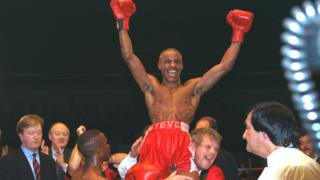 Boxer Steve Robinson smiles and has his arms in the air as he his lifted high by one of his trainers.