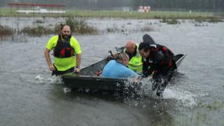 Rescuers with a resident in a boat in North Carolina