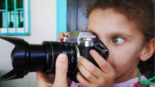 Refugee girl with camera