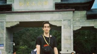 Phillip Hancock posing in front of a tourist attraction in China