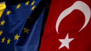 Turkish flag hands next to EU flag