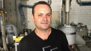Dimitris Koumatsioulis is pictured in a factory setting, with industrial drums visible in the background