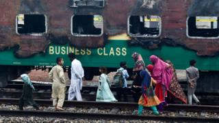A family walks passed the charred remains of a train carriage