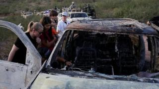 Relatives of slain members of Mexican-American families belonging to Mormon communities observe the burnt wreckage of a vehicle where some of their relatives died