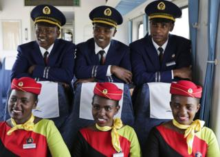 Kenya Railways train attendants (R) pose for a photograph inside one of the new passenger trains