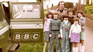 Andrew Sachs stops for a photo with local children during a BBC recording