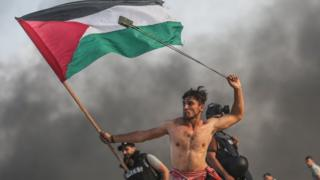 Palestinian holding a flag and swinging a sling