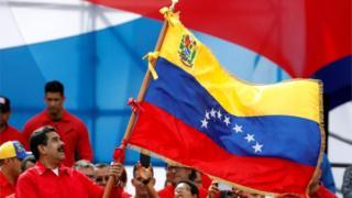 مادورو يحمل علم فنزويلا