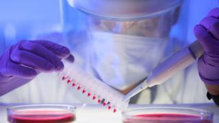 Científico con traje protector en el laboratorio