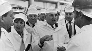 O ex-presidente soviético Mikhail Gorbachev (ao centro) e sua esposa Raisa Gorbacheva (à esq.) conversam com trabalhadores na usina nuclear em fevereiro de 1989, pouco antes do desastre