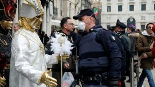 Police officer wearing a protective face mask stands next to carnival revellers at Venice Carnival. 23 Feb 2020