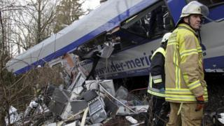 Rescuers stand in front of a carriage at the site of the two crashed trains