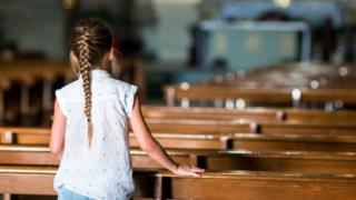 Girl standing in pews of a church