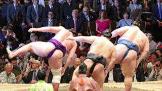 US President Donald Trump, his wife, Melania, and Japanese PM Shinzo Abe watch Sumo Wrestlers perform