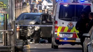 Australian police stand near a crashed vehicle that had ploughed into pedestrians near Flinders Street train station in central Melbourne, Australia, December 21, 2017
