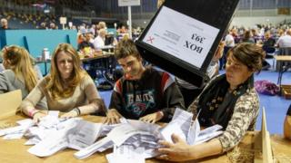 Staff count ballot papers at the Glasgow count centre at the Emirates Arena