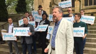 People with Yorkshire Party placards standing on steps